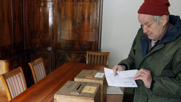 Ein Senior vor einer Abstimmungsurne im Kanton Uri