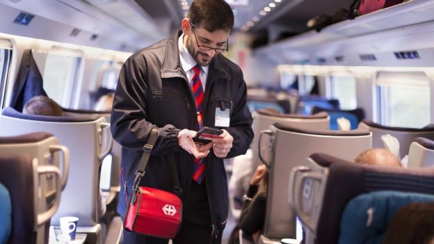 Ein Kondukteur kontrolliert die Billete der Passagiere in einem Zug der SBB.