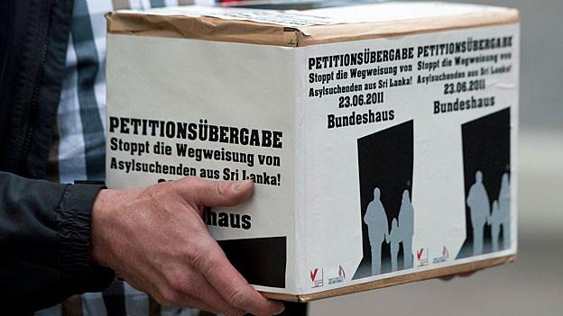 Auf einer Schachtel steht: «Petitionsübergabe. Stoppt die Wegweisung von Asylsuchenden aus Sri Lanka. 23.06.2011. Bundeshaus».