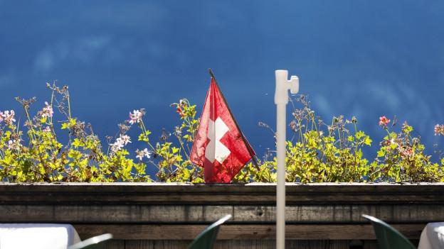 Eine Schweizer Fahne weht auf einem sommerlichen Balkon