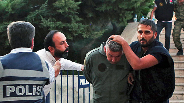 Ein Zivilist spuckt einen verhafteten türkischen Armeeangehörigen an.