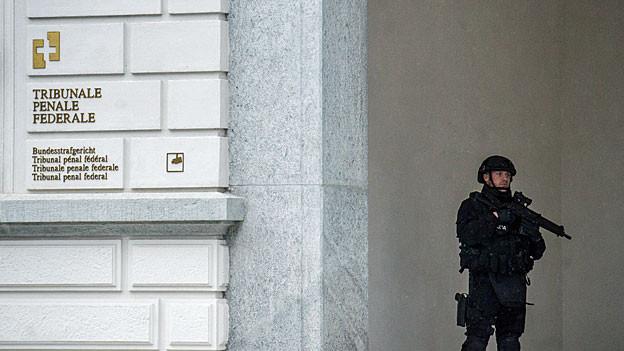 Ein schwer bewaffneter Polizist bewacht während des Prozesses gegen die IS-Anhänger den Eingang zum Bundesstrafgericht in Bellinzona.