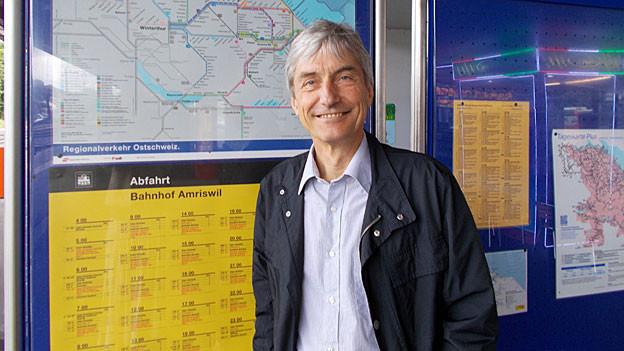 Jürg Brühlmann steht vor einem Fahrplan und einem Ortsplan mit den Regionalverkehrslinien am Bahnhof Amriswil.