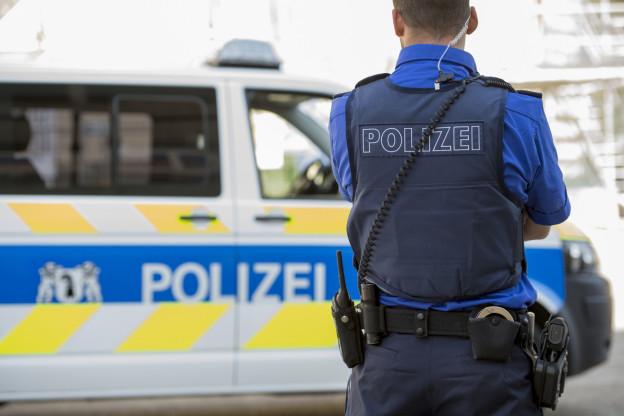 Ein Polizist steht vor einem Polizeiauto, an seinem Gurt ist das Waffenholster zu sehen.