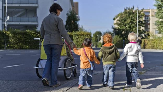 Eine Tagesmutter geht mit drei kleinen Kindern in einer Siedlung spazieren.