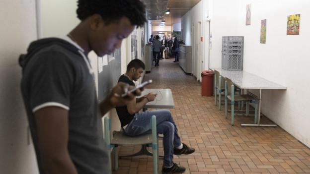 Junge Männer in einem Gang, auf die Handys starrend.