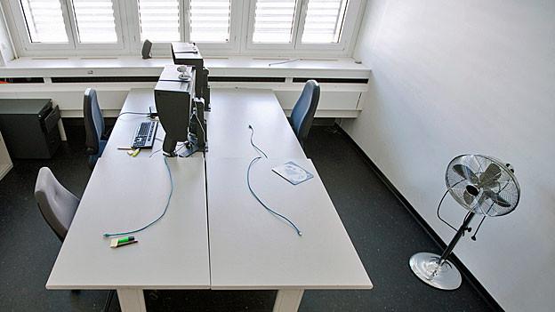 Ein leerer Stuhl steht vor einem leeren Schreibtisch.