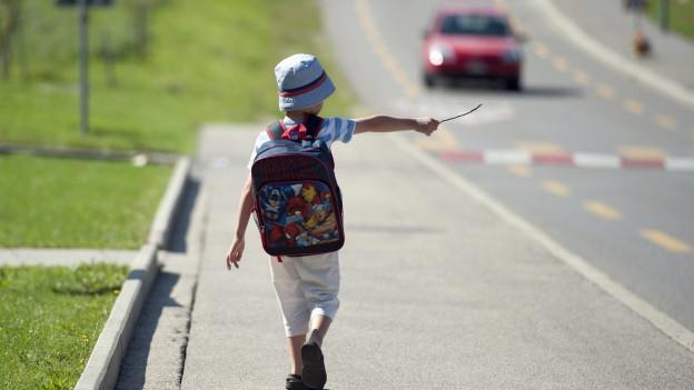 Ein Junge unterwegs auf seinem Schulweg.