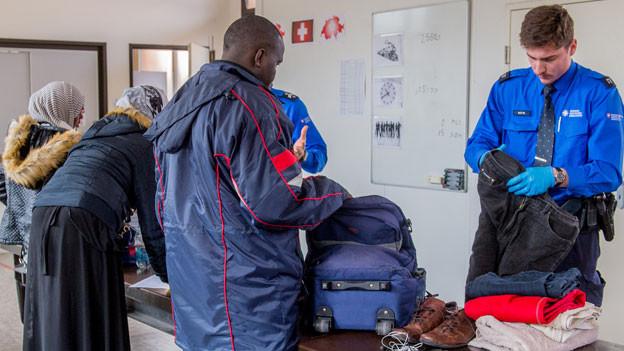Flüchtlinge und Personal des Grenzwachtkorps bei der Grenzkontrolle am Zoll des Bahnhofs Chiasso.