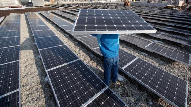 Ein Mann hält ein Solarpanel in die Luft
