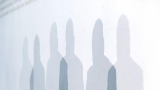 Die Schatten von Mitgliedern der Wettbewerbskommission WEKO während ihrer Jahresmedienkonferenz im April in Bern