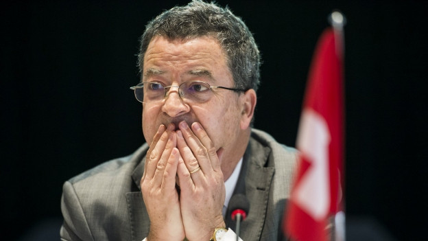 Ein Mann mit Brille sitzt neben einer kleinen Schweizer Flagge, die Hände hat er über den Mund gelegt.