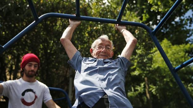 Ein älterer Herr turnt auf einem Klettergerüst herum
