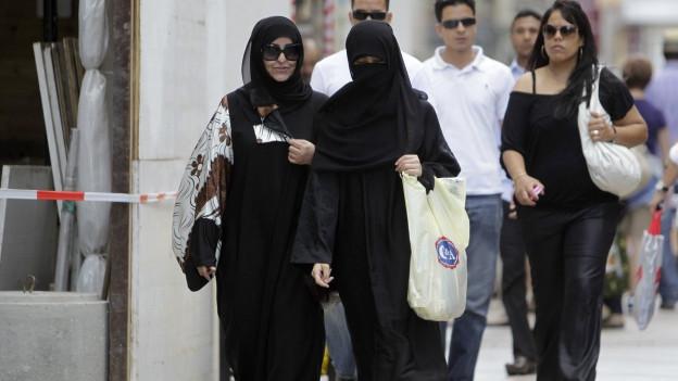 Zwei Musliminnen gehen durch die Strasse, eine ist von Kopf bis Fuss verhüllt, die andere trägt Kopftuch und Sonnenbrille.