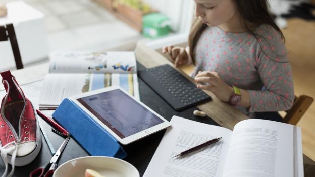 Hefte, Tabletcomputer und andere Schulutensilien liegen auf einem Tisch, dazu ein Turnschuh und ein Teller mit Apfelschnitzen, ein Mädchen sitzt am Tisch und tippt.