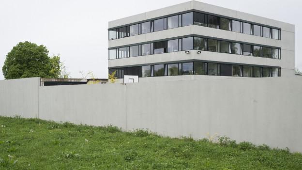 Das Empfangs- und Verfahrenszentrum Kreuzlingen hinter einer Betonmauer mit Wiese im Vordergrund.