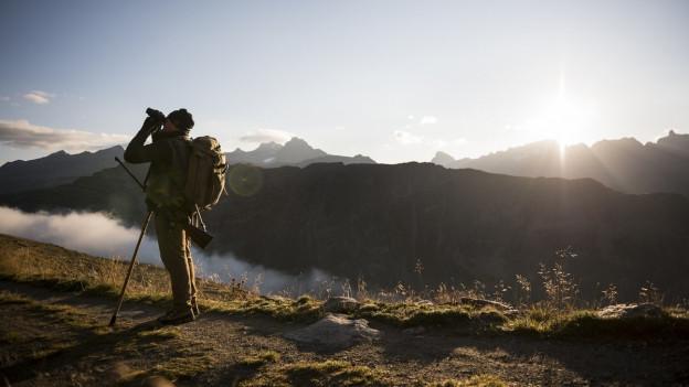 Ein Jäger schaut vor einer Bergkulisse durch sein Fernglas. Hinter ihm geht gerade die Sonne auf.