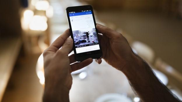 Das Bild zeigt einen Asylbewerber von hinten, der auf ein Handy schaut.
