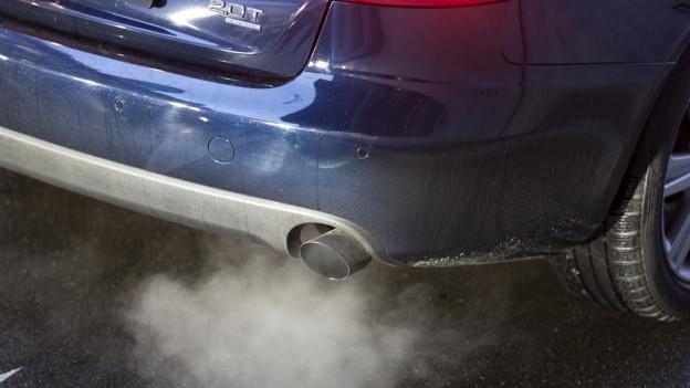 Der Auspuff eines Autos stösst Qualm aus.