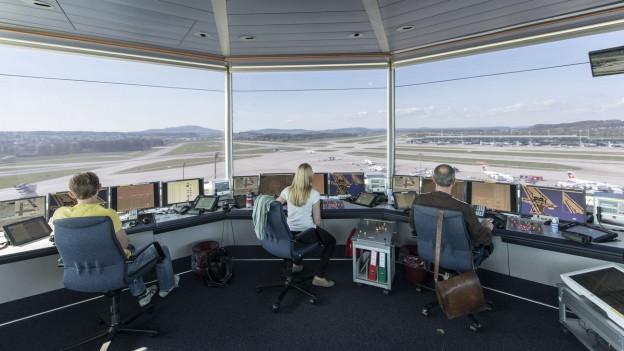 Im Bild sieht man drei Mitarbeiter, welche im Skyguide Tower in Zürich die Flugpisten überblicken.