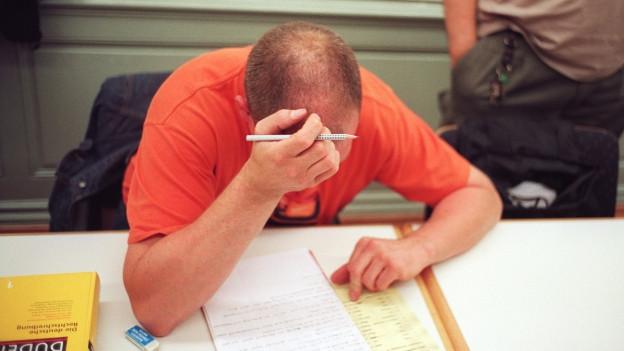 Mann beugt sich über Text, angestrengt.