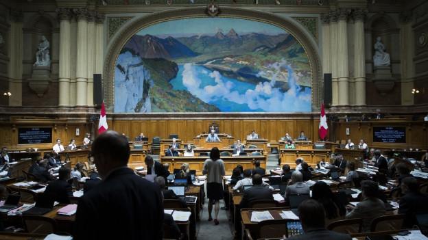 Aufnahme aus dem Nationalratssaal, im Hintergrund das Rednerpult, im Vordergrund die Umrisse mehrerer Politiker.
