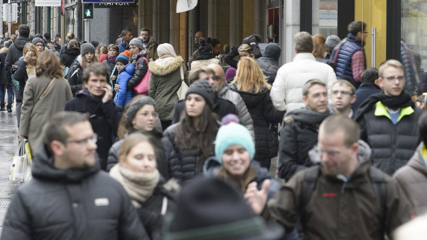 Menschen laufen eine Einkaufsmeile entlang.