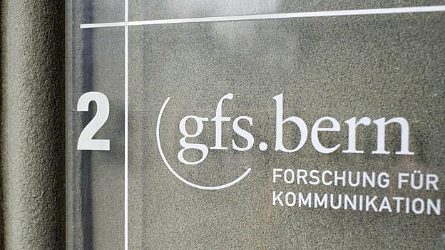 «gfs.bern» steht an einer Glastüre.