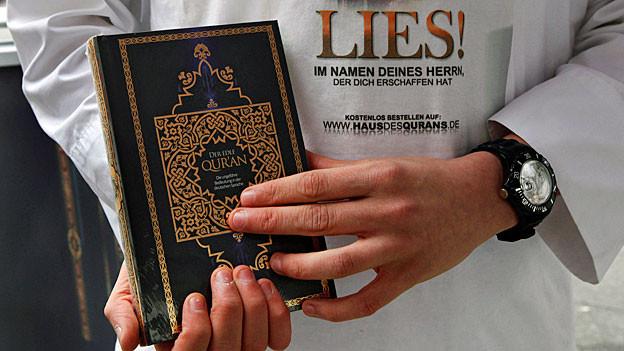 Ein Mann hält einen Koran vor der Brust; auf seinem T-Shirt steht: «Lies!».