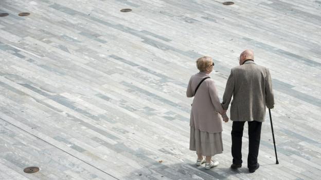 Ein Rentnerpaar passiert den Sechseläutenplatz in Zürich.