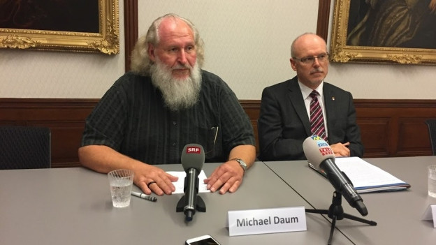 Michael Daum und Bürgergemeindepräsident Wyniger am Tisch mit Mikrofonen.