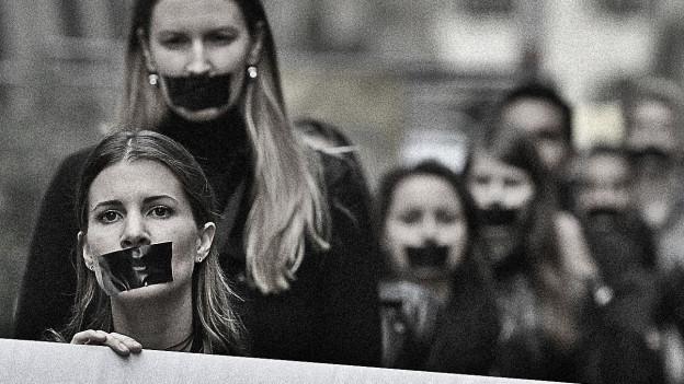 Demonstrierende Frauen in schwarz gekleidet, die sich den Mund mit einem Stück schwarzen Klebeband zugeklebt haben.