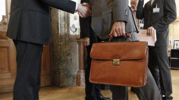 Zwei Männer geben sich im Bundeshaus die Hand.