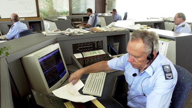 Polizeibeamter mi Headset und Computer in Notrufzentrale