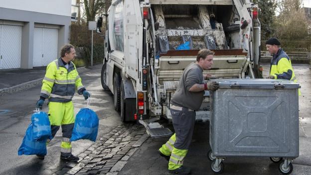 Städtische Angestellte sammeln Abfallsäcke ein.