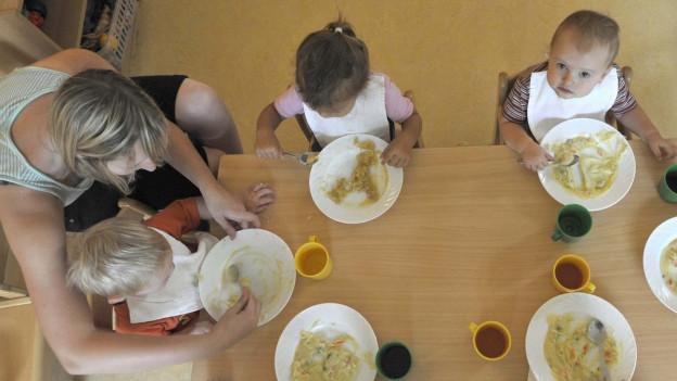 Kleinkinder beim Mittagessen in einer Kita.
