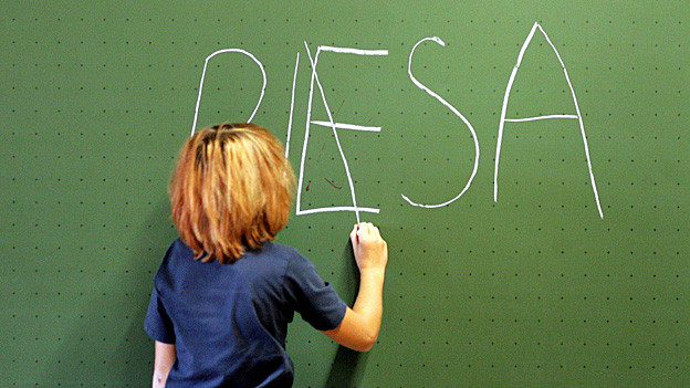 «PIESA» steht auf einer Wandtafel. Ein Mädchen streicht das E durch.