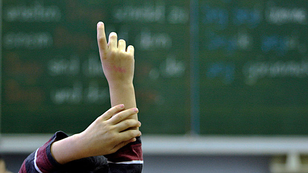 Ein Schüler hebt in einem Schulzimmer die Hand.