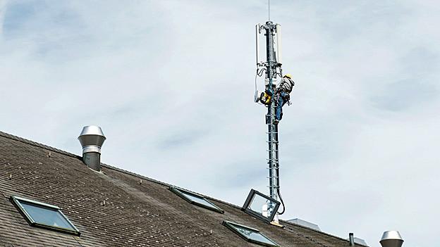 Ein Mann arbeitet an einer Mobilfunkantenne, die auf einem Dach montiert ist.