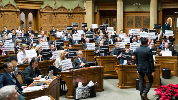 Nationalräte der SVP halten bei der Schlussabstimmung über die Masseneinwanderungsinitiative im Nationalrat Plakate hoch mit der Aufschrift «Verfassungsbruch» und «Massenzuwanderung geht weiter».