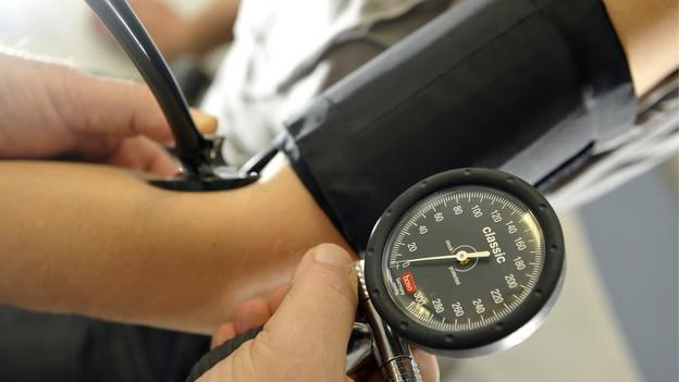 Blutdruckmessgerät an einem Arm.