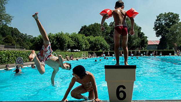 Kinder vergnügen sich am Rande eines Schwimmbeckens.