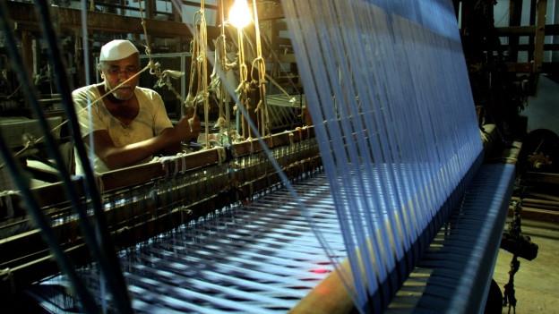 Ein Mann steht hinter einem Webstuhl in einer Fabrik