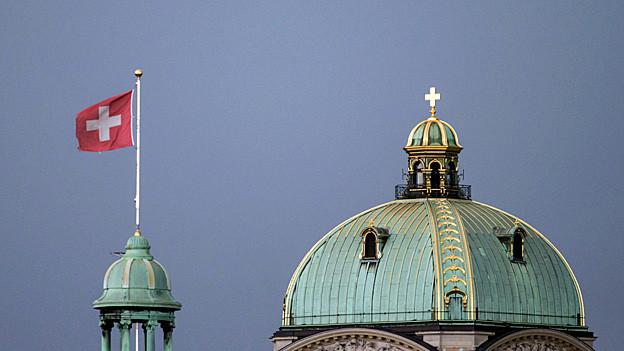 Neben der Kuppel des Bundeshauses weht eine Schweizer Fahne.