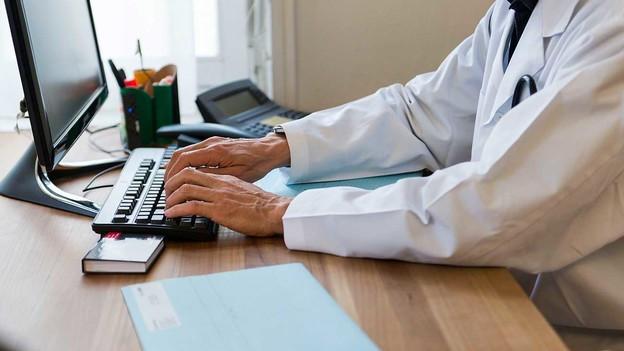 Ein Mann in einem Arztkittel sitzt an einem Computer.