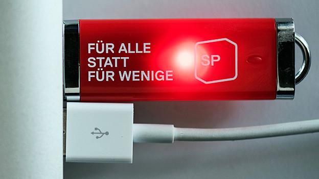 «Für alle statt für wenige» steht in weissen Buchstaben auf eine roten USB-Stick, einem Werbeartikel der SP.