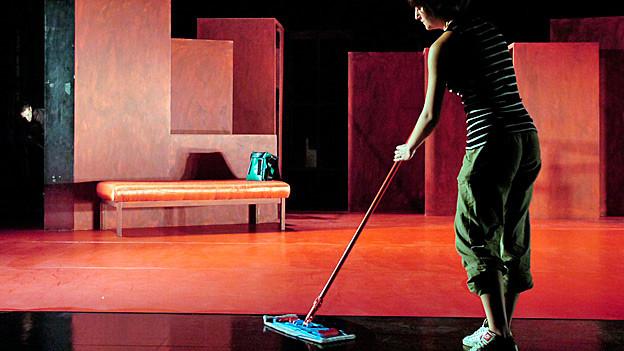 Eine Raumpflegerin wischt den Boden einer Theaterbühne.