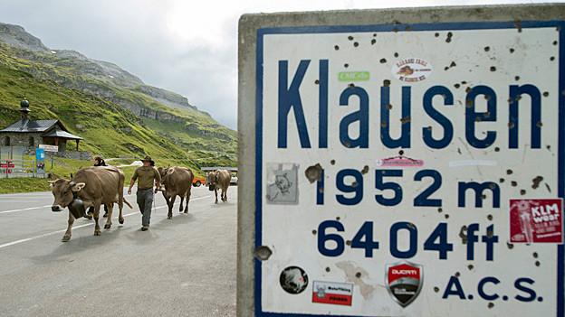 «Klausen 1952 m 6404 ft» steht in dunkelblauen Buchstaben auf einem weissen Schild.
