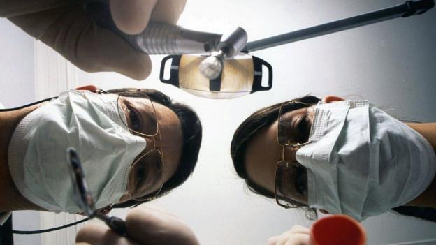 Das Bild zeigt zwei Zahnärzte, die sich über den Patienten beugen.