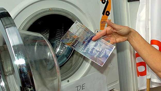 Eine Hand steckt eine riesengrosse Tausend-Franken-Note in eine Waschmaschine.